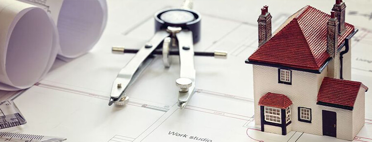 Blueprint, small model home, and pencil marking compass