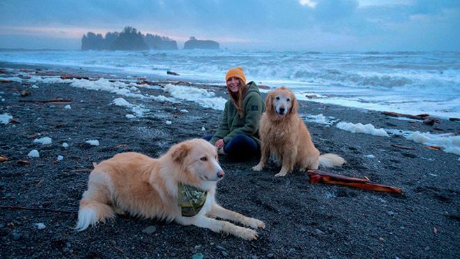 A woman dressed in warm clothes sits on a Pacific Northwest beach with two dogs